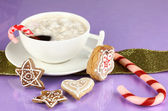 Cup of coffee with Christmas sweetness on purple background — Photo