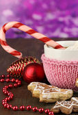 Cup of coffee with Christmas sweetness on wooden table on purple bokeh background — Photo
