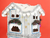 Decorated Christmas house on red background — Stock Photo