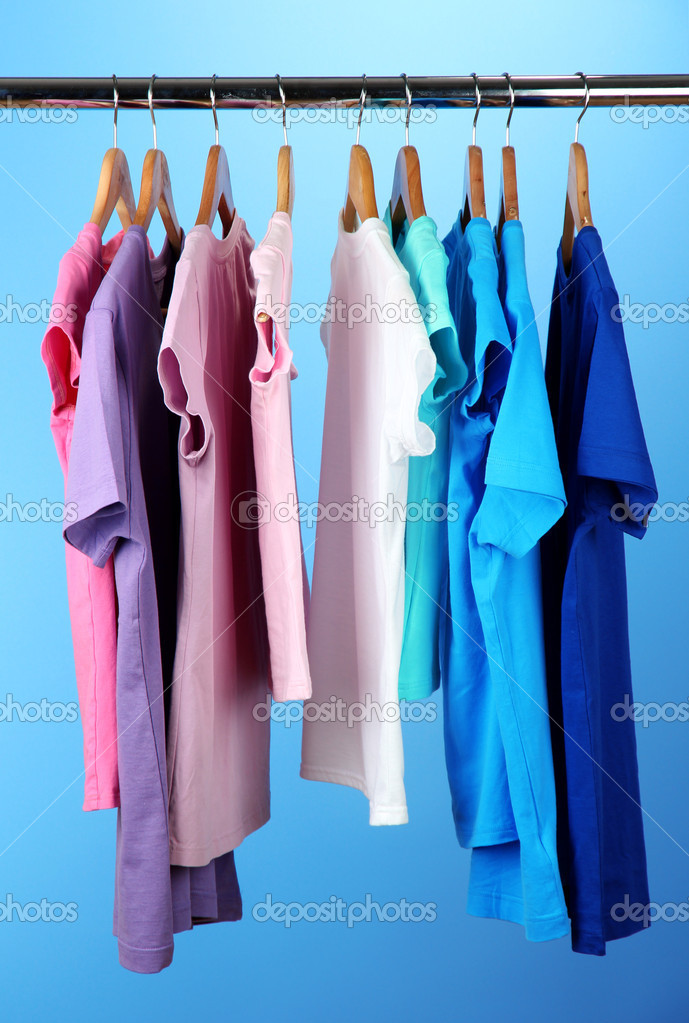 Variety of casual shirts on wooden hangers,on blue background — Stock Photo #18040263