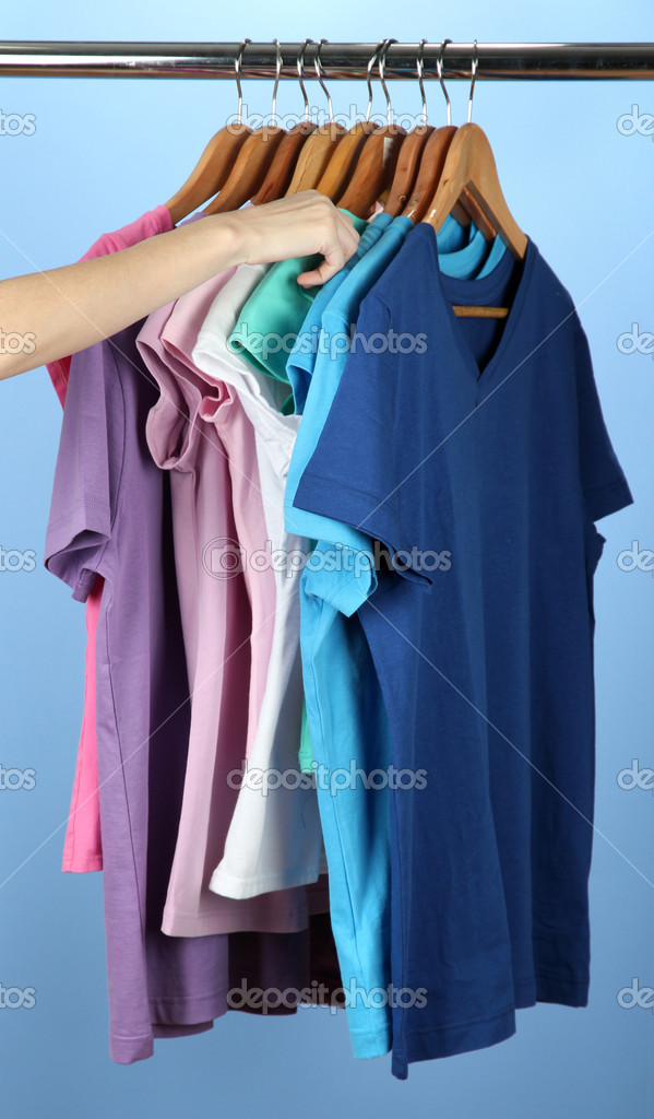Variety of casual shirts on wooden hangers,on blue background — Stock Photo #18040267
