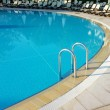 Stock Photo: Hotel swimming pool with sunny reflections