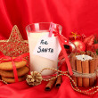 Cookies for Santa: Conceptual image of ginger cookies, milk and christmas decoration on red background — Stock Photo #18051589