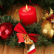 Stock Photo: Christmas composition with candle and decorations in red and gold colors on wooden background