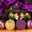 Stock Photo: Christmas composition with candles and decorations in purple and gold colors on wooden background