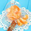 Tangerine's slices on saucer under glass cover on blue background - Stock Photo