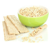 Green bowl full of oat flakes with wooden scoop and oat biscuits isolated on white — Stock Photo