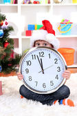 Child with clock in anticipation of New Year — Stock Photo