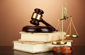Golden scales of justice, gavel and books on brown background — Stock Photo