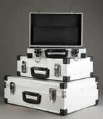 Silvery suitcases on grey background — Stock Photo