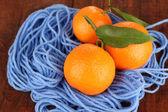Doces tangerinas com folhas, sobre fundo azul fio — Fotografia Stock