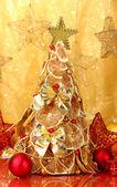 Linda árvore de natal de limões secos com decoração, sobre fundo amarelo — Fotografia Stock