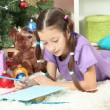 Little girl writing letter to Santa near christmas tree — Stock Photo #18061809