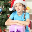 Little girl holding gift box near christmas tree — Stock Photo #18061811