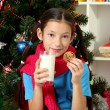 Little girl with pink scarf and glass of milk sitting near christmas tree — Stock Photo #18061821