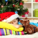 Little girl sleeping near christmas tree — Stock Photo #18061823