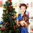 Little girl holding toy near christmas tree — Stock Photo