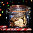 Tasty cookies in glass bottle on blur lights background — Stock Photo #18061873