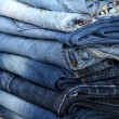 Stock Photo: Many jeans stacked in pile closeup