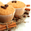 Tasty muffin cakes on burlap, spices and coffee seeds, isolated on white — Stock Photo #18063931