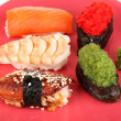 Delicious sushi served on red plate close-up - Stock Photo