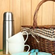 Metal thermos with cups, plates and basket on grass on wooden background — Stock Photo #18064161
