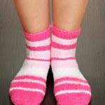 Legs female in striped socks on laminate floor — Stock Photo #18064321