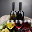 Bottles and glasses of wine and grapes on grey background — Stock Photo #18064409