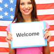 Young woman young woman holding tablet on background of American flag — Stock Photo #18064879