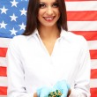 Portrait of female doctor or scientist showing and analyzing pills over American Flag background — Stock Photo