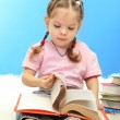 Cute little girl with colorful books, on blue background — Stock fotografie