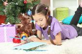 Liten flicka skriva brev till santa nära julgran — Stockfoto