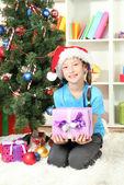 Kleines mädchen hält geschenk-box in der nähe von weihnachtsbaum — Stockfoto