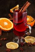 Duftenden glühwein glas mit gewürzen und orangen um auf holztisch — Stockfoto
