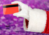Santa Claus hand holding red credit card on purple background — Stock Photo