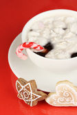 Cup of coffee with Christmas sweetness on red background — Stock Photo