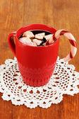 Tasse Kaffee mit Urlaub Candy auf Holztisch Nahaufnahme — Stockfoto