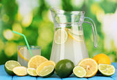 Citrus lemonade in pitcher and glass of citrus around on natural wooden table on blue background — Stock Photo