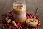 Delicious peanut butter in jar on wooden table close-up — Stock Photo