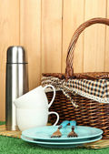 Metal thermos with cups, plates and basket on grass on wooden background — Stock Photo