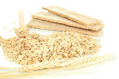 Oat flakes in wooden spoon with spikelets and oat biscuits isolated on white — Stock Photo