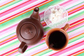 Top view of cup of tea and teapot on colorful tablecloths — Stock Photo