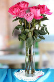 Beautiful pink roses in vase on blue fabric table on room background — Stock Photo