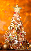 Beautiful christmas tree of dry lemons with decor, on orange background — Stock Photo