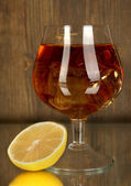 Glass of brandy with ice and lemon on wooden background — Stock Photo