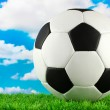 Stock Photo: Football ball on green grass, on blue sky background