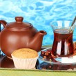 Glass of Turkish tea and kettle on color background - Stok fotoğraf