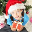 Little girl holding gift box near christmas tree — Stock Photo #18106441