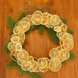Christmas wreath of dried lemons with fir tree and stars, on wooden background — ストック写真