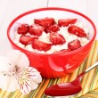Cottage cheese in red bowl with sliced strawberries on white wooden table - Stock Photo